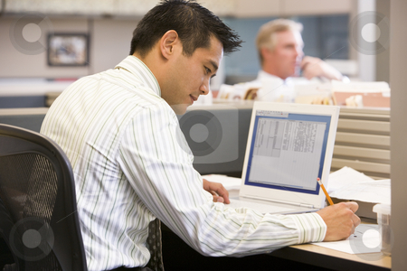 Businessman in cubicle with laptop writing stock photo,  by Monkey Business Images