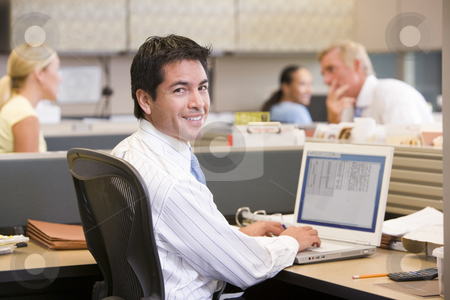 Businessman in cubicle with laptop smiling stock photo,  by Monkey Business Images