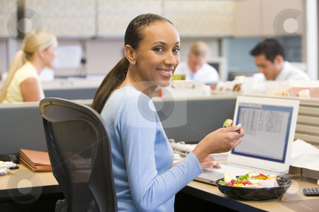 Businesswoman in cubicle with laptop eating salad stock photo,  by Monkey Business Images