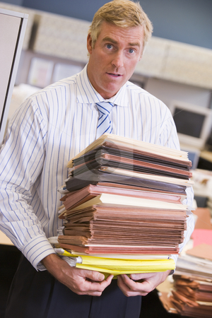 Businessman standing in cubicle with stacks of files stock photo,  by Monkey Business Images