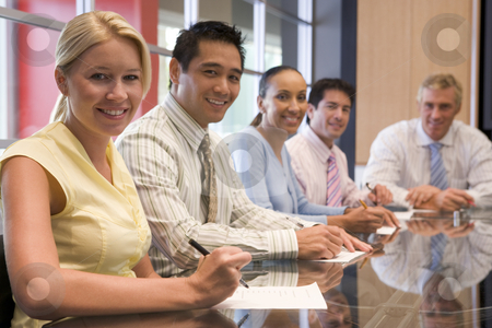Five businesspeople in boardroom smiling stock photo,  by Monkey Business Images