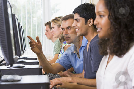 Teacher assisting college student in a computer lab stock photo,  by Monkey Business Images