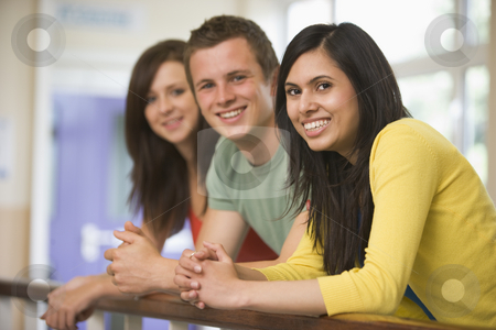 Three college students leaning on banister stock photo,  by Monkey Business Images