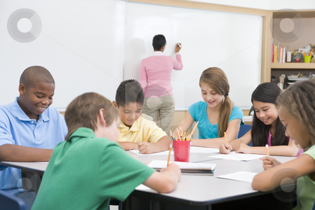 Elementary school clasroom with teacher stock photo, Elementary school clasroom with teacher writing on board by Monkey Business Images