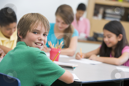 Elementary school pupil at desk stock photo,  by Monkey Business Images