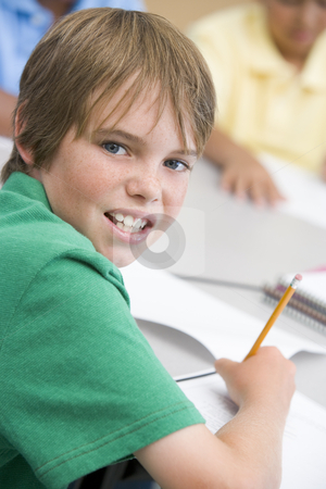 Elementary school pupil writing stock photo, Elementary school pupil writing in book by Monkey Business Images