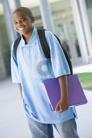 Elementary school pupil outside stock photo, Elementary school pupil outside carrying folder by Monkey Business Images