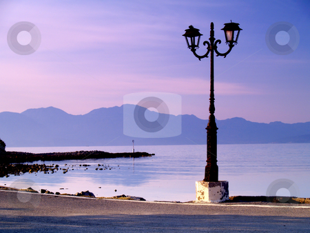 Lantern at the waterfront stock photo, Lantern in early morning light at elounda, crete, greece by Torsten Lorenz