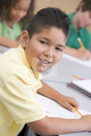 Male pupil in elementary school classroom stock photo, Male pupil in elementary school classroom writing at desk by Monkey Business Images