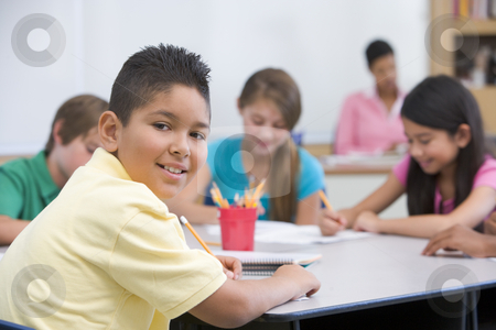Elementary school pupil in classroom stock photo, Male elementary school pupil in classroom by Monkey Business Images