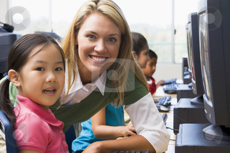Teacher helping kindergarten children learn how to use computers stock photo,  by Monkey Business Images