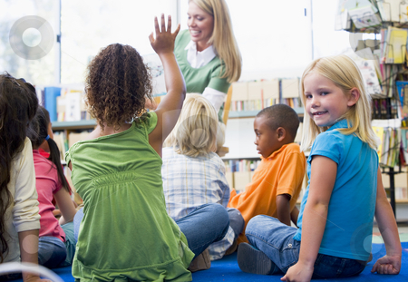 Kindergarten teacher reading to children in library, girl lookin stock photo,  by Monkey Business Images