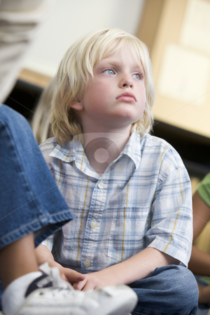 Boy daydreaming at kindergarten stock photo,  by Monkey Business Images