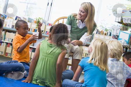 Kindergarten teacher and children looking at seedling in library stock photo,  by Monkey Business Images