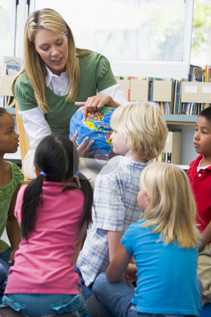 Kindergarten teacher and children looking at globe stock photo,  by Monkey Business Images