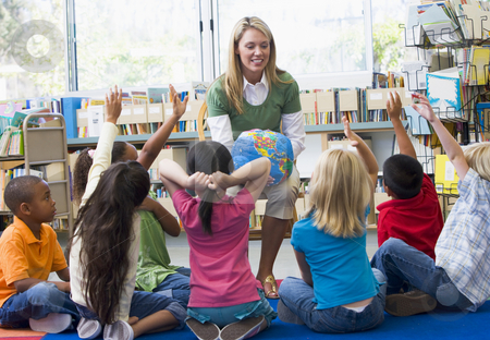 Kindergarten teacher and children with hands raised in library stock photo,  by Monkey Business Images