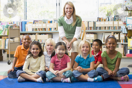 Kindergarten teacher sitting with children in library stock photo,  by Monkey Business Images