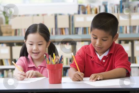 Kindergarten children sitting at desk and writing in classroom stock photo,  by Monkey Business Images