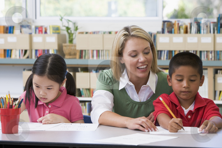 Kindergarten teacher helping students with writing skills stock photo,  by Monkey Business Images