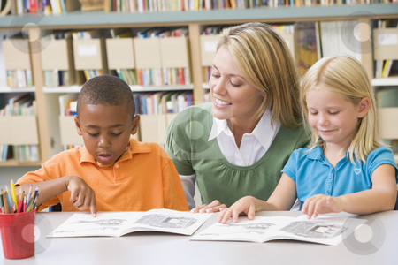 Kindergarten teacher helping students with reading skills stock photo,  by Monkey Business Images