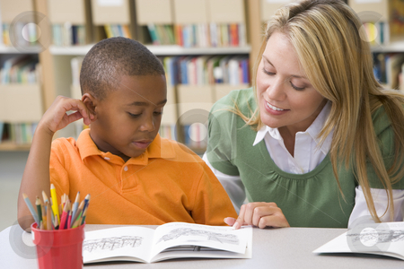 Kindergarten teacher helping student with reading skills stock photo,  by Monkey Business Images