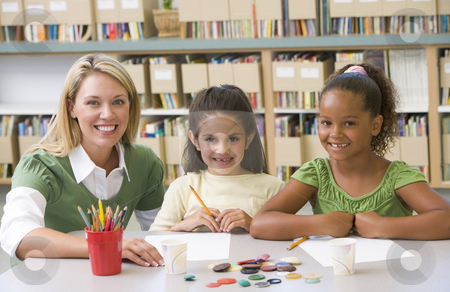 Kindergarten teacher sitting with students in art class stock photo,  by Monkey Business Images