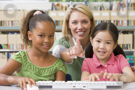 Kindergarten teacher sitting with children at computer  stock photo,  by Monkey Business Images