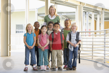 Kindergarten teacher standing with children in corridor stock photo,  by Monkey Business Images
