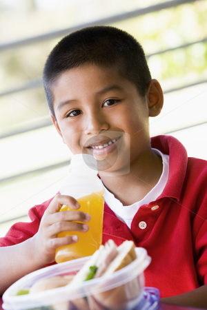 Boy eating lunch at kindergarten stock photo,  by Monkey Business Images