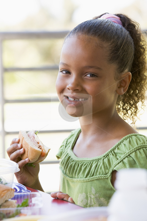 Girl eating lunch at kindergarten  stock photo,  by Monkey Business Images