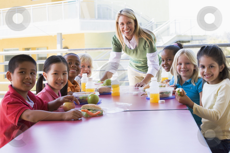 Kindergarten teacher supervising children eating lunch stock photo,  by Monkey Business Images