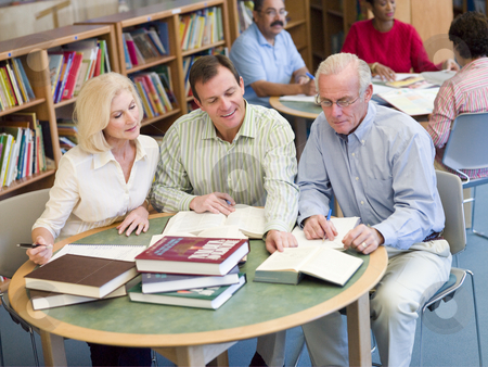 Mature students studying together in library  stock photo,  by Monkey Business Images