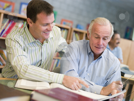 Tutor assisting mature student in library stock photo,  by Monkey Business Images