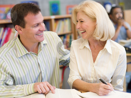 Mature student laughing with tutor in library stock photo,  by Monkey Business Images