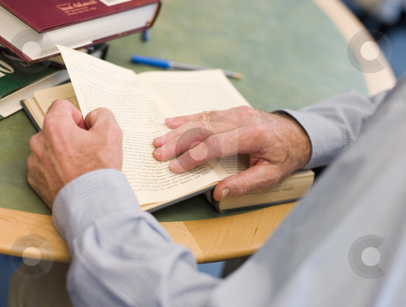 Close-up of mature student's hands turning book page in library stock photo,  by Monkey Business Images
