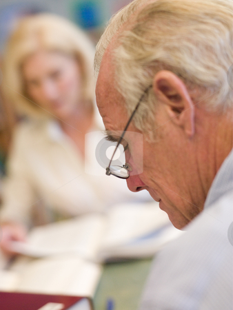 Mature students studying in library stock photo,  by Monkey Business Images