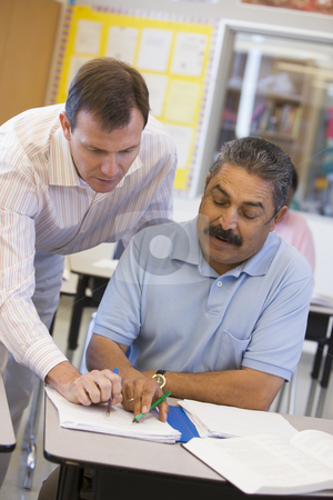 Teacher assisting mature student in class stock photo,  by Monkey Business Images