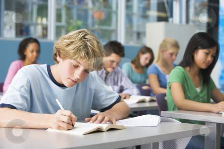 Schoolboy in high school class stock photo,  by Monkey Business Images