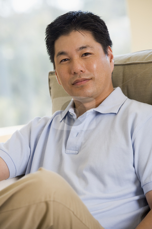 Man sitting in living room stock photo,  by Monkey Business Images