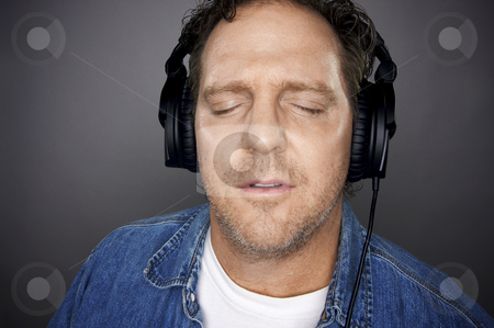 Man With Headphones stock photo, Man with Eyes Shut Wearing Headphones Enjoying His Music on a Grey Background. by Andy Dean