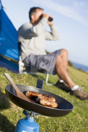 Man camping outdoors and cooking stock photo,  by Monkey Business Images