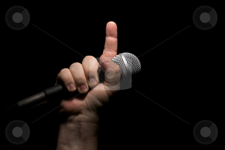 Microphone in Fist stock photo, Microphone clinched firmly in male fist with index finger pointing up. by Andy Dean