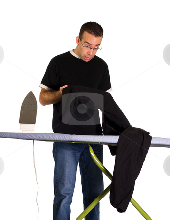 Ironing Mistake stock photo, A man looking at a spot on his pants where he left the iron too long by Richard Nelson
