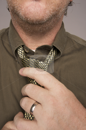 Man Fixing Tie stock photo, Man Fixing Tie Against Grey Background by Andy Dean