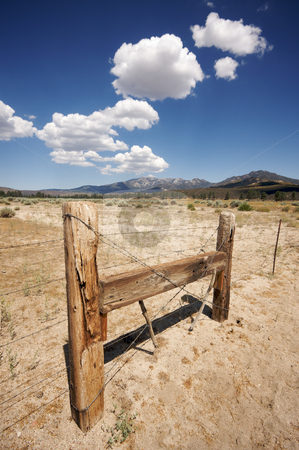 Aged Fence and Clouds stock photo, Puffy Storm Clouds Forming Over Field and Aged Fence on a blue sky. by Andy Dean