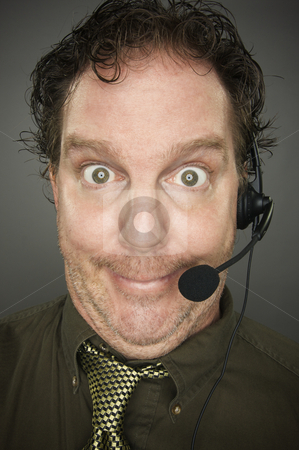 Giddy Businessman stock photo, Giddy Businessman Smiles Wearing a Phone Headset Against a Grey Background. by Andy Dean