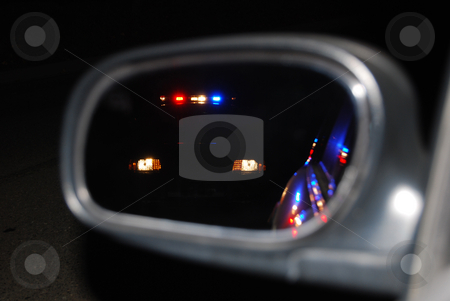 Reflection stock photo, Police car making a stop in the side view mirror at night. by Steven Kapinos