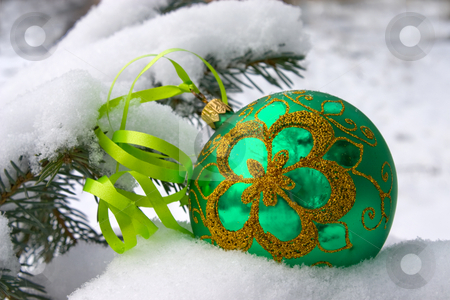 Christmas time. stock photo, A green christmas bauble sitting in a bed of snow. by Yury Ponomarev