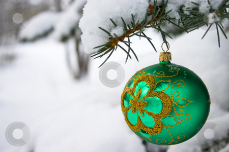 Christmas time. stock photo, Green  christmas glass ball hanging on the tree in snow. by Yury Ponomarev