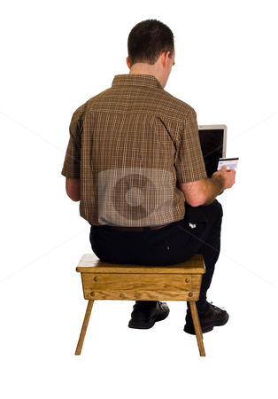 Online Shopping stock photo, A man sitting on a stool doing some online shopping with a credit card by Richard Nelson